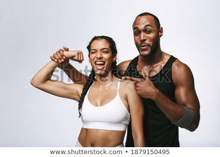 Sport couple standing and showing biceps together Stock photo © deandrobot