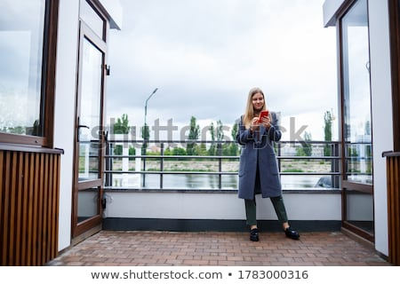 beautiful blonde girl sitting at the lake stock photo © konradbak