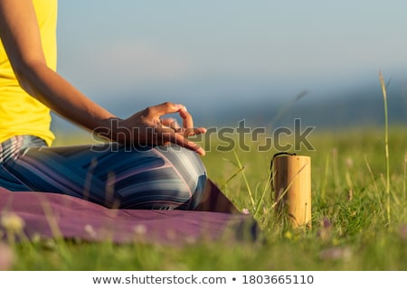 Woman sitting and meditating on yoga mat outdoors Stock photo © deandrobot