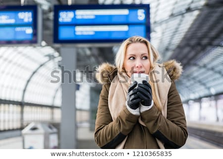 Woman in train station in winter warming up with a hot coffee Stock photo © Kzenon