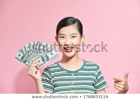 Photo of happy woman in basic clothing holding fan of dollar mon Stock photo © deandrobot