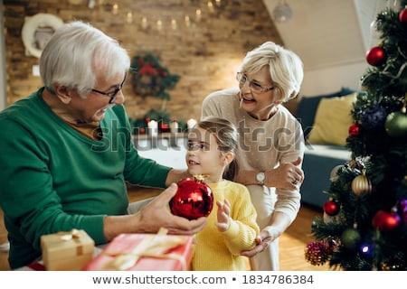 happy senior woman decorating christmas tree stock photo © dolgachov