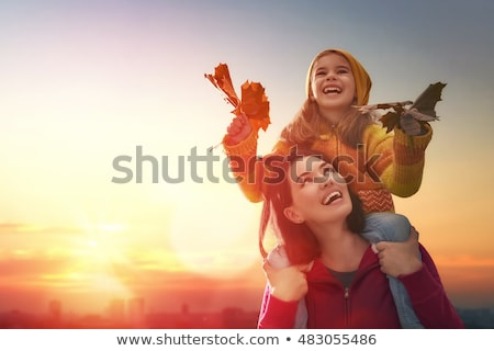 Mother and her little daughter play cuddling on autumn walk in n Stock photo © dashapetrenko