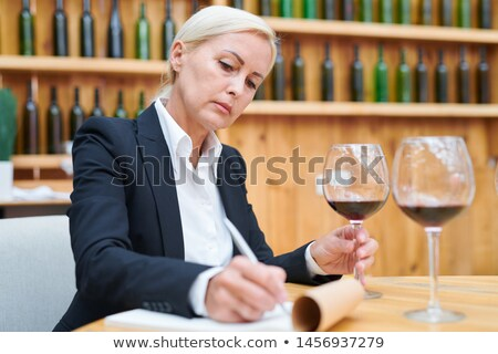 Experienced winery expert making notes about characteristics of red wine Stock photo © pressmaster