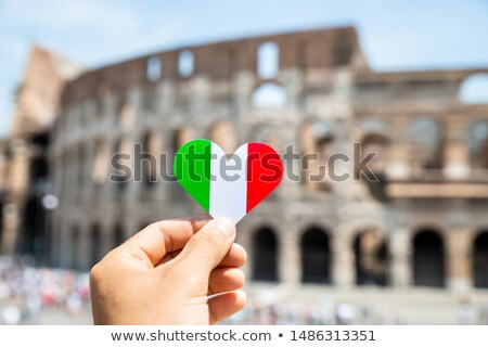 woman holding heart shaped italian flag in front of colosseum stock photo © andreypopov