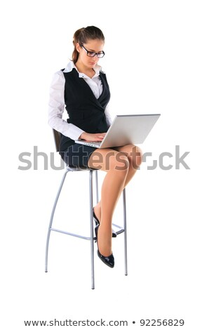 Pretty elegant businesswoman with laptop sitting on desk and surfing in the net Stock photo © pressmaster