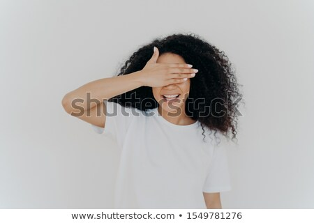 Stock photo: Young teen lady covers eyes with palm, hides herself, smiles toothy, has Afro bushy hairstyle, wears