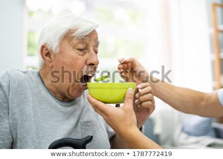Hungry Elder Patient Being Feed Stock photo © AndreyPopov