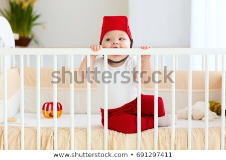 toddler with teether sitting in cot Stock photo © phbcz
