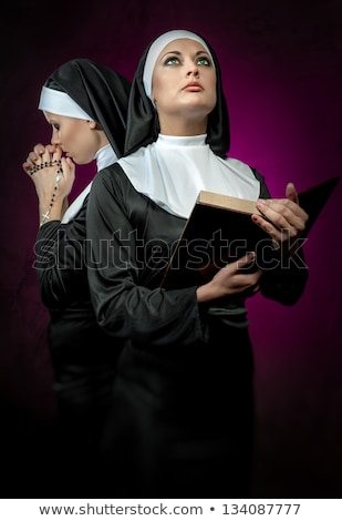 two attractive young nuns with rosary and bible praying stock photo © amok