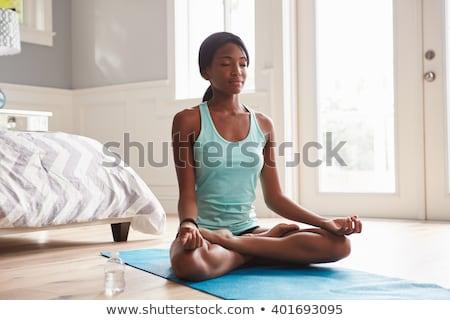 Young woman doing yoga lotus position Stock photo © sumners