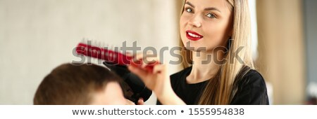 Young hairdresser drying man's hair with blowdryer  Stock photo © deandrobot
