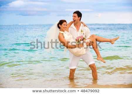 Attractive bride and groom getting married by the beach Stock photo © deandrobot