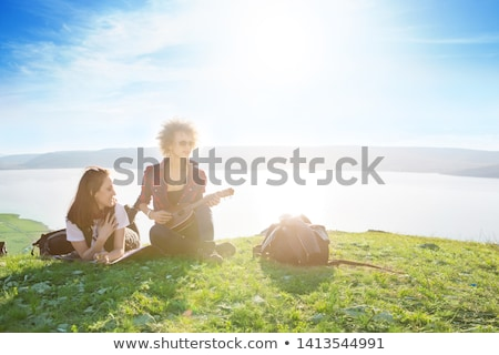 Pretty young woman sitting on mountain top and contemplating lan Stock photo © Yatsenko