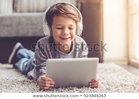 smiling boy using digital tablet while listening to headphones on sofa at home stock photo © wavebreak_media