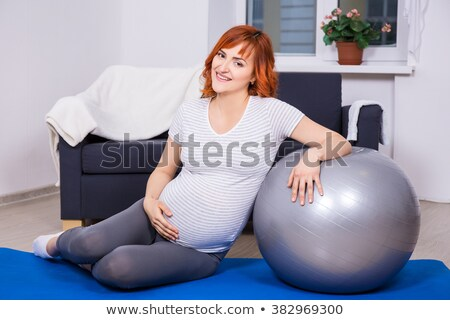 Happy pregnant woman sitting on fitball and doing exercise Stock photo © deandrobot
