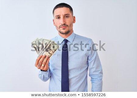 Portrait of a serious confident man holding bunch of money Stock photo © deandrobot