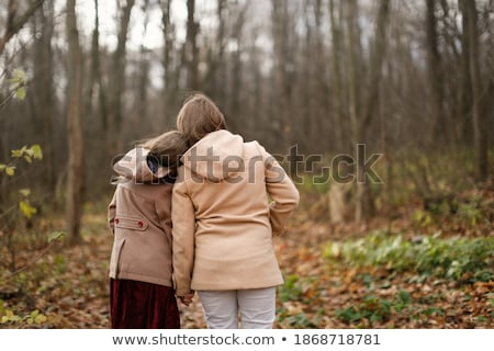 Stock photo: Two beautiful girlfriends at the autumn park near tree.
