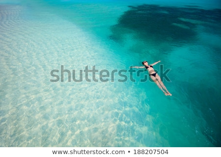 Young woman floating on blue water surface. Stock photo © Sonya_illustrations