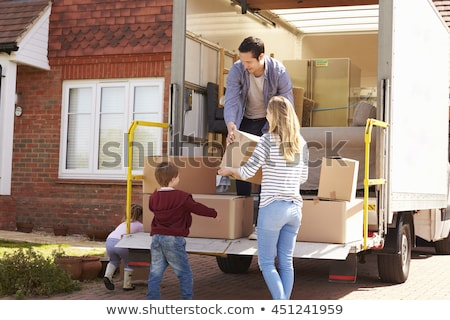 Family unpacking boxes from moving van Stock photo © IS2