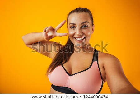 Portrait of chubby sportswoman in sportive bra using mobile phon Stock photo © deandrobot