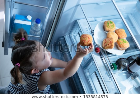 Girl Trying To Take Cupcake From The Refrigerator Stock photo © AndreyPopov