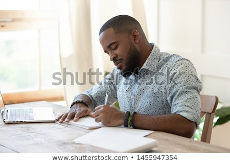 Young inspired professional with pen making notes or sketching Stock photo © pressmaster