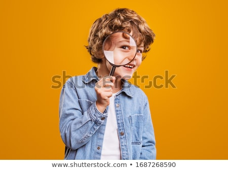 Stock photo: Boy looking in a magnifying glass against the background of the garden. Home schooling