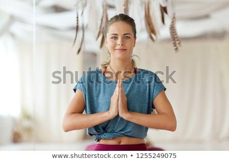 woman with namaste gesture at yoga studio Stock photo © dolgachov