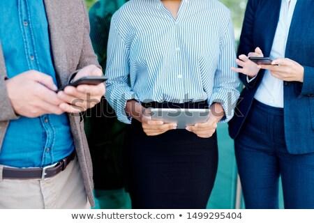 Drie jonge elegante collega's mobiele gadgets Stockfoto © pressmaster