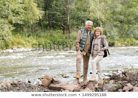 Affectionate mature spouses with backpacks standing on stones on river bank Stock photo © pressmaster