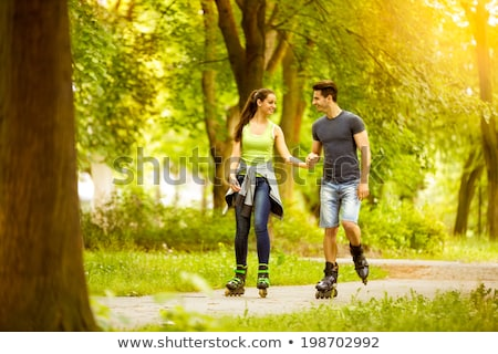 couple with roller skates riding in summer park stock photo © dolgachov