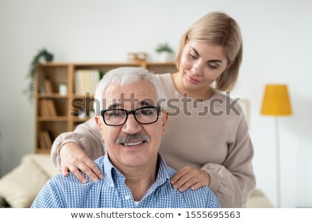Careful young woman doing massage of shoulders to her senior father at home Stock photo © pressmaster