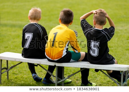 Friends on a Soccer Team Sitting on a Wooden Bench. Group of Interracial  Kids in a School Sports Te Stock photo © matimix