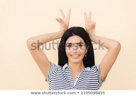 Portrait of happy brunette female makes horn gesture, has fun and foolishes with friends, being in g Stock photo © vkstudio