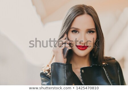 Close up shot of lovely woman talks with friend via mobile app, has makeup and red lips, dressed in  Stock photo © vkstudio