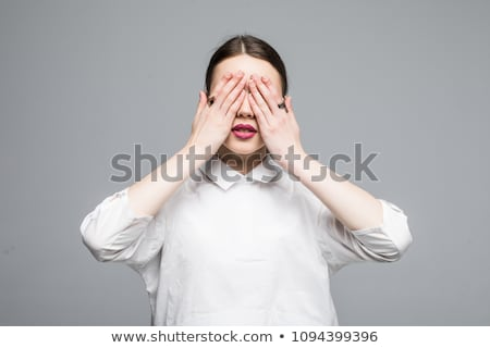 Beautiful young woman covering her mouth with both hands stock photo © williv