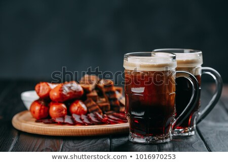 Dark beer in glass and two grilled sausages Stock photo © karandaev