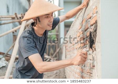 Mason spreading cement on brick Stock photo © photography33