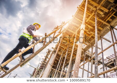 worker wearing hard hat climbing ladder stock photo © stockyimages