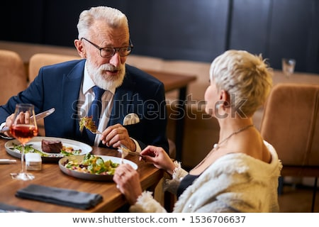 Senior couple eating dinner in restaurant stock photo © Kzenon