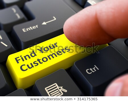 pressing yellow button find your customers on black keyboard stock photo © tashatuvango