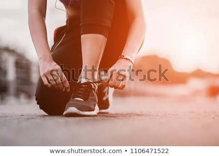 Stockfoto: Young Sporty Woman Tying Shoe Laces Outdoors