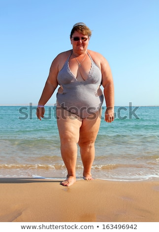 Woman standing in swimwear on beach Stock photo © Kzenon