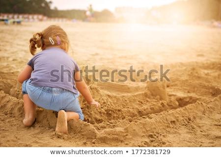 Girl kneeling on beach in water Stock photo © Kzenon