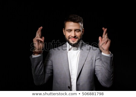 Handsome peaceful man in dark suit praying Stock photo © deandrobot