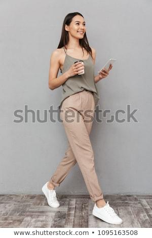 full length portrait of a smiling asian businesswoman walking stock photo © deandrobot