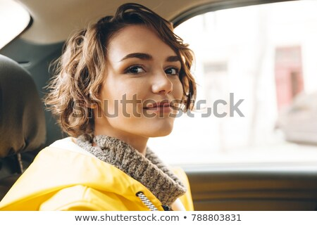 pretty young lady dressed in raincoat sitting in car stock photo © deandrobot