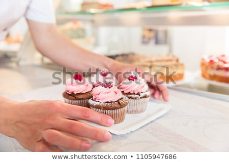 Women putting muffins on display in bakery shop Stock photo © Kzenon