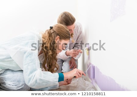 two female worker giving purple color on the wall stock photo © kzenon